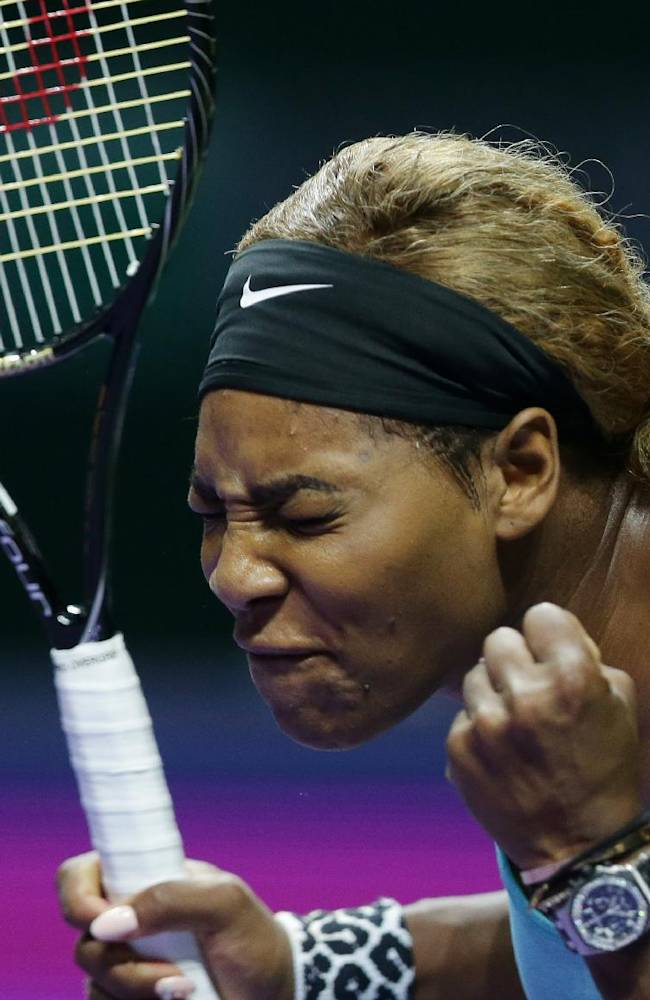 In this Wednesday, Oct. 22, 2014 photo, Serena Williams of the U.S. reacts during her singles match against Romania's Simona Halep at the WTA tennis finals in Singapore