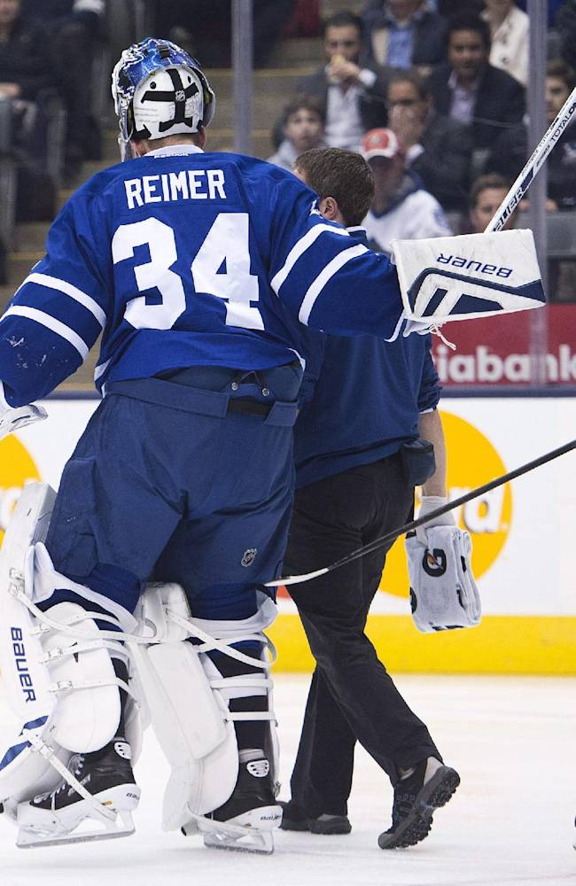 Toronto Maple Leafs goalie James Reimer, left, leaves the game after being injured as Dion Phaneuf, right, trails, during the first period of an NHL hockey game against the Carolina Hurricanes in Toronto on Thursday, Oct. 17, 2013