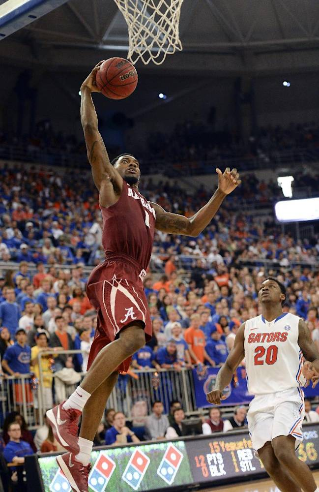Alabama's Algie Key goes to the basket for two points with Florida guard Michael Frazier II (20) unable to stop the shot during the second half of an NCAA college basketball game Saturday, Feb. 8, 2014 in Gainesville, Fla. Florida won 78-69