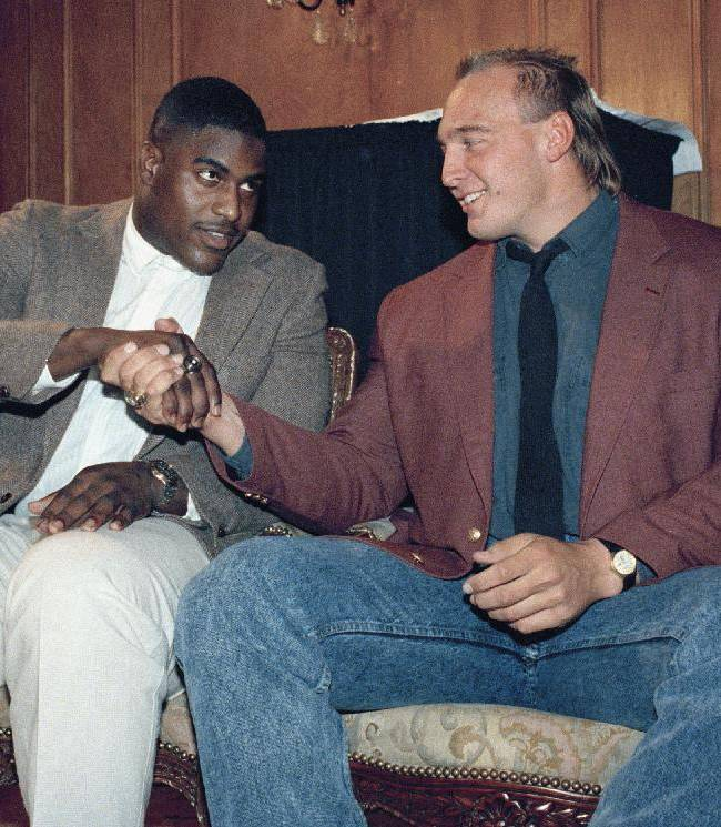 In this Dec. 7, 1988, file photo, Auburn's Tracy Rocker, center, the winner of the 1988 Outland Trophy, gets a congratulatory handshake from runner-up Tony Mandarich, right, of Michigan State, at a ceremony in New York.  What, exactly, is a college education worth? For some players, an athletic scholarship was their only means of going to college. Tuition, even at a state school, was too expensive, and that scholarship meant the difference between higher education and a blue-collar job or a career in the military. More than that, however, were the experiences and contacts their education provided _ opportunities that helped shape their adult lives