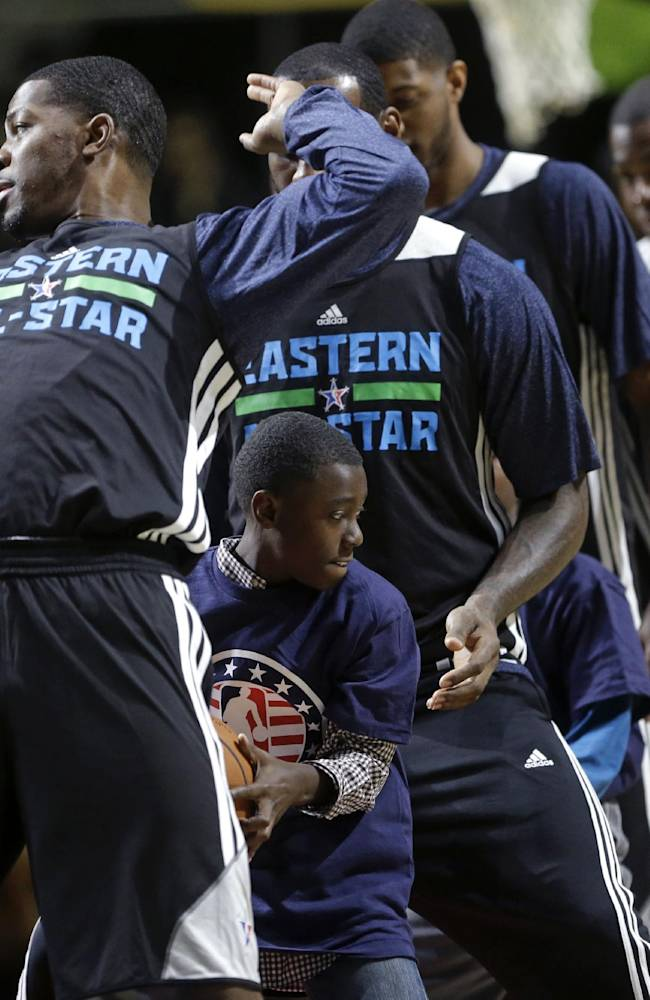 Team East's Joe Johnson, of the Brooklyn Nets, passes the ball to a youngster during a fan participation at basketball practice for the NBA All-Star game in New Orleans, Saturday, Feb. 15, 2014
