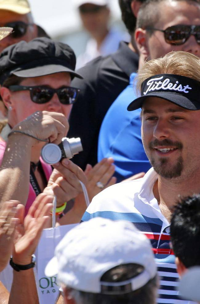 Victor Dubuisson of France is welcomed by supporters as he arrives for the first day of the French Open Golf tournament at Paris National course in Guyancourt, west of Paris, France, Thursday, July 3, 2014