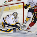 Nashville Predators goalie Pekka Rinne, of Finland, and Calgary Flames' Mikael Backlund (11), of Sweden, vie for control of the puck during the first period of an NHL hockey game in Calgary, Alberta, Friday, March 21, 2014 The Associated Press