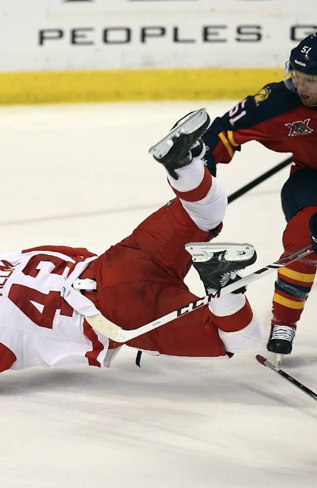 Detroit Red Wings' Darren Helm (43) falls to the ice as Florida Panthers' Brian Campbell (51) and Jonathan Huberdeau (11) apply pressure during the second period of an NHL hockey game in Sunrise, Fla., Thursday, Feb. 6, 2014