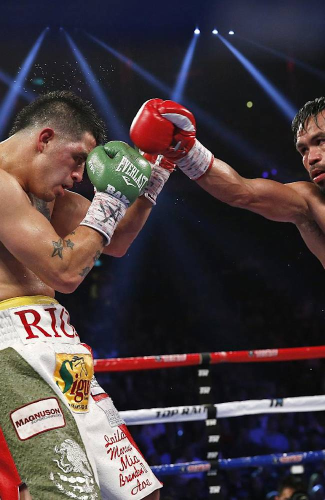 Manny Pacquiao, from the Philippines, right, punches Brandon Rios of the United States during their WBO international welterweight title fight Sunday, Nov. 24, 2013, in Macau. Pacquiao defeated Rios by unanimous decision on Sunday to take the WBO international welterweight title and return to his accustomed winning ways after successive defeats