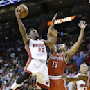 Miami Heat guard Norris Cole (30) goes up to shoot against Milwaukee Bucks guard Ramon Sessions (13) during the first half of an NBA basketball game on Wednesday, April 2, 2014, in Miami The Associated Press