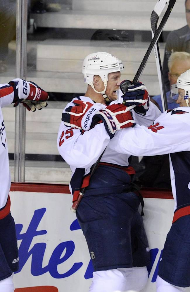 Washington Capitals' Jason Chimera, center, celebrates his goal against the Calgary Flames with Eric Fehr, left. and Mikhail Grabovski, from Germany, during the first period of an NHL hockey game, in Calgary, Alberta, Saturday, Oct. 26, 2013