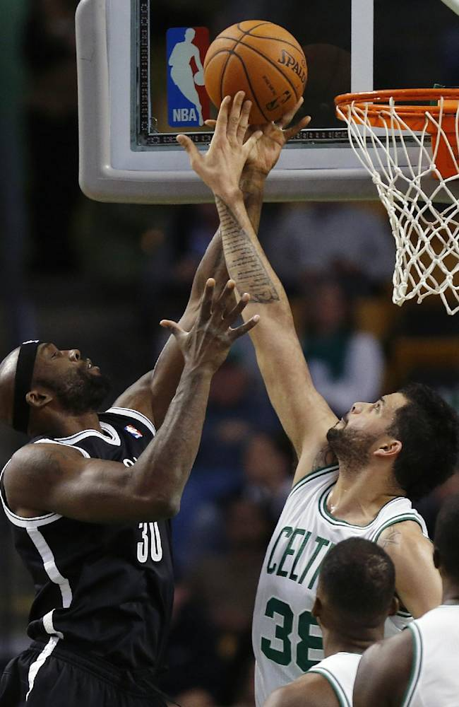Boston Celtics' Vitor Faverani (38) blocks the shot by Brooklyn Nets' Reggie Evans (30) in the first quarter of a preseason NBA basketball game in Boston, Wednesday, Oct. 23, 2013
