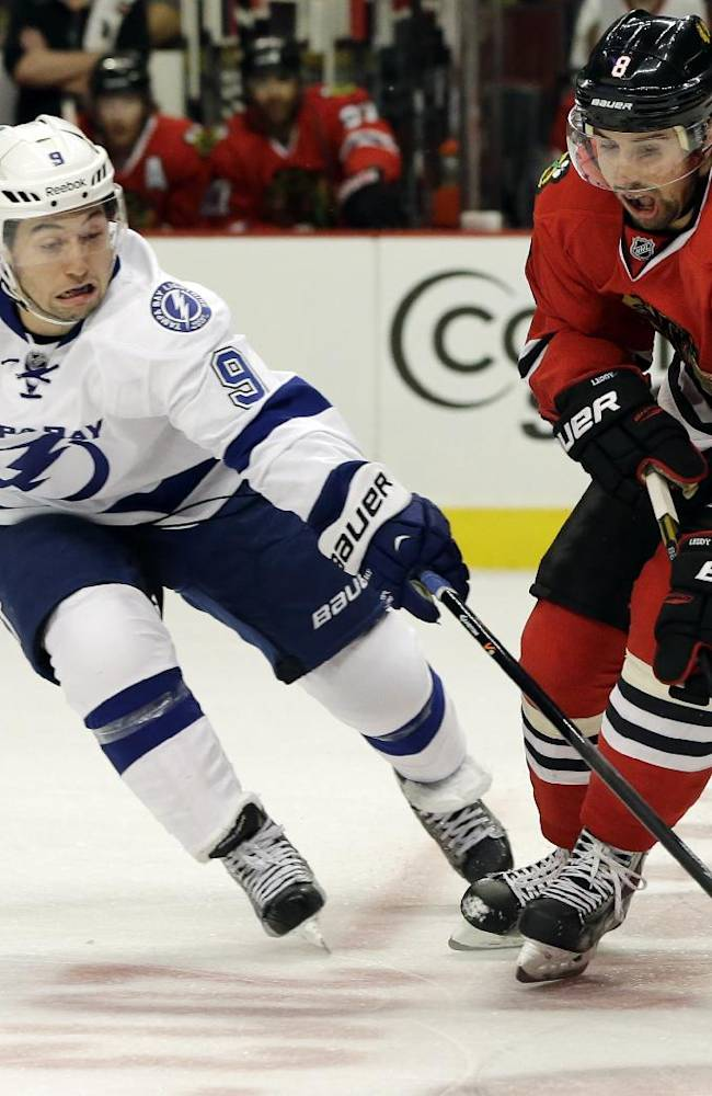 Tampa Bay Lightning's Tyler Johnson, left, and Chicago Blackhawks' Nick Leddy (8) vie for the puck during the first period of an NHL hockey game in Chicago, Saturday, Oct. 5, 2013