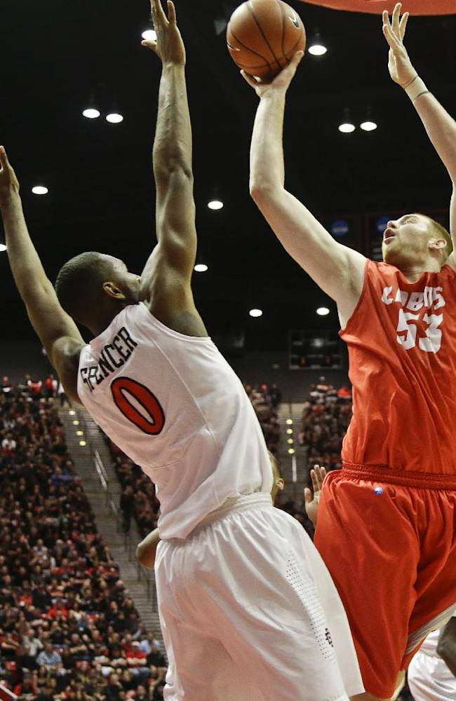 New Mexico center Alex Kirk scores over San Diego State forward Skylar Spencer during the second half of a NCAA college basketball game Saturday, March 8, 2014, in San Diego. New Mexico built a 14 point lead only to lose 51-48 and San Diego State captured the Mountain West Conference regular season championship