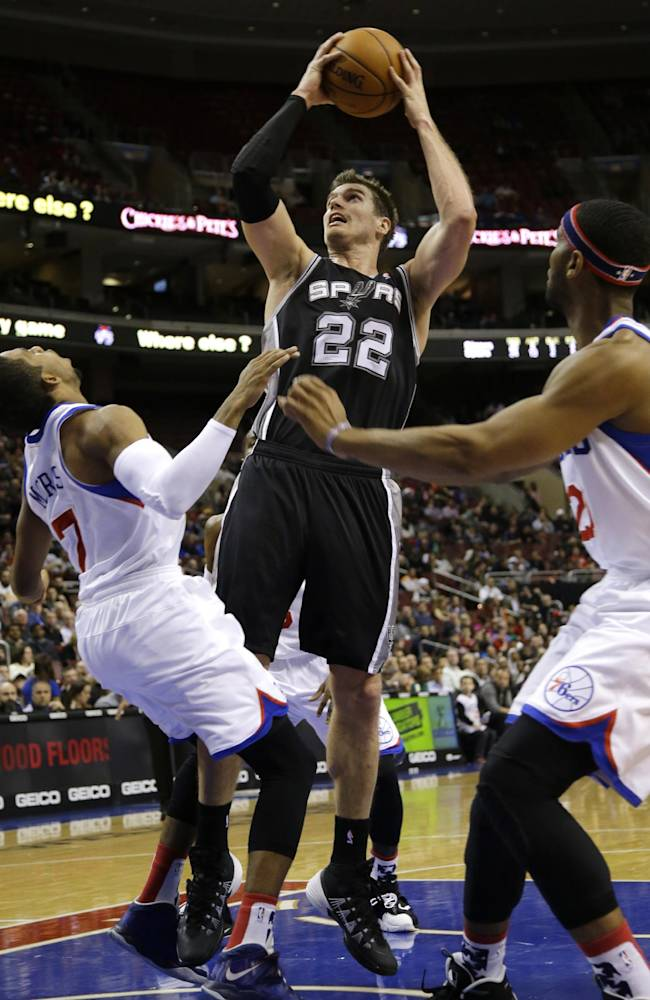 San Antonio Spurs' Tiago Splitter, center, of Brazil, goes up for a shot as Philadelphia 76ers' Darius Morris, left, and Brandon Davies defend during the first half of an NBA basketball game, Monday, Nov. 11, 2013, in Philadelphia