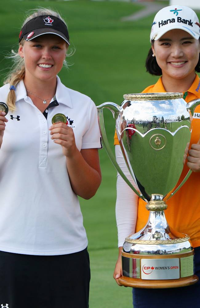 Brooke Henderson, left, of Canada, holds medals for the Top Canadian and the Top Amateur and poses with winner So Yeon Ryu, of South Korea, at the Canadian Pacific Women's Open golf tournament in London, Ontario, Sunday, Aug. 24, 2014