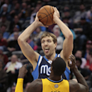 Dallas Mavericks forward Dirk Nowitzki (41) holds the ball away from Denver Nuggets center J.J. Hickson (7) in the second quarter of an NBA game in Denver on Wednesday, March 5, 2014 The Associated Press