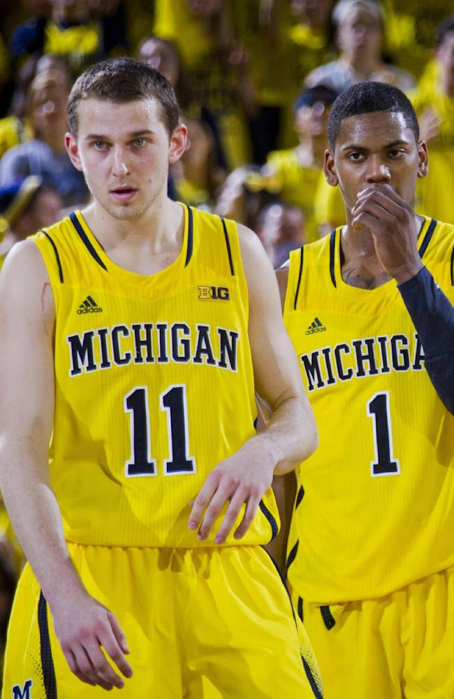 In this Feb. 23, 2014 file photo, Michigan guard Nik Stauskas (11), and forward Glenn Robinson III (1) stand on the court after a time out in the second half of an NCAA college basketball game against Michigan State, at Crisler Center in Ann Arbor, Mich. Sophomores Robinson and Stauskas helped the Wolverines win the Big Ten title and reach an  NCAA tournament regional final last season