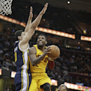 Cleveland Cavaliers' Kyrie Irving, center, jumps to the basket against Utah Jazz's Enes Kanter, left, from Turkey, and Alec Burks, right, during the third quarter of an NBA basketball game on Friday, Feb. 28, 2014, in Cleveland The Associated Press