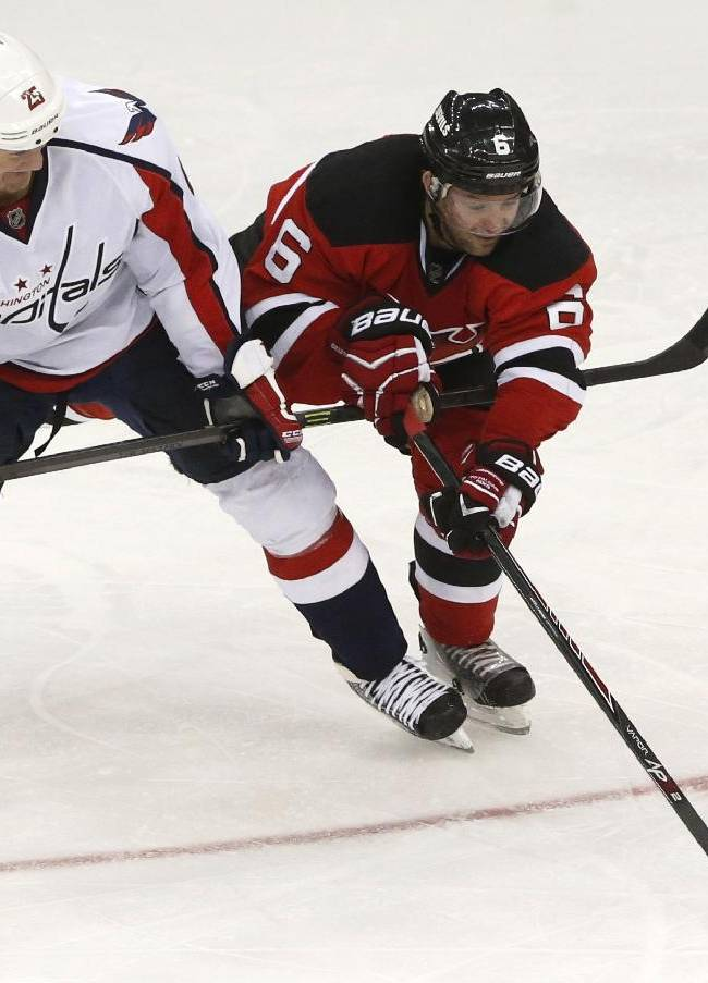 Washington Capitals left wing Jason Chimera (25) and New Jersey Devils defenseman Andy Greene (6) compete for the puck during the third period of an NHL hockey game, Friday, April 4, 2014, in Newark, N.J. The Devils won 2-1
