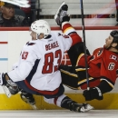 Washington Capitals' Jay Beagle, left, checks Calgary Flames' Dennis Wideman during the second period of an NHL hockey game Saturday, Oct. 25, 2014, in Calgary, Alberta The Associated Press