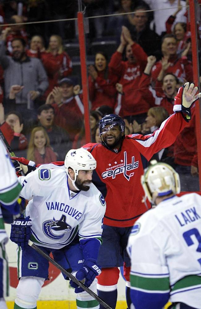 Washington Capitals right wing Joel Ward, back, celebrates his goal as Vancouver Canucks goalie Eddie Lack (31) and Jason Garrison (5) react during the first period of an NHL hockey game, Friday, March 14, 2014, in Washington