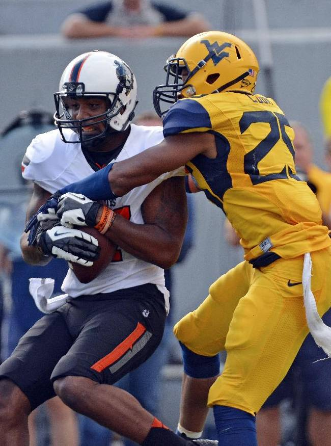 Oklahoma State receiver Tracy Moore (87) is tackled by West Virginia defender Darwin Cook (25) in the third quarter of an NCAA college football game in Morgantown, W.Va., on Saturday, Sept. 28, 2013