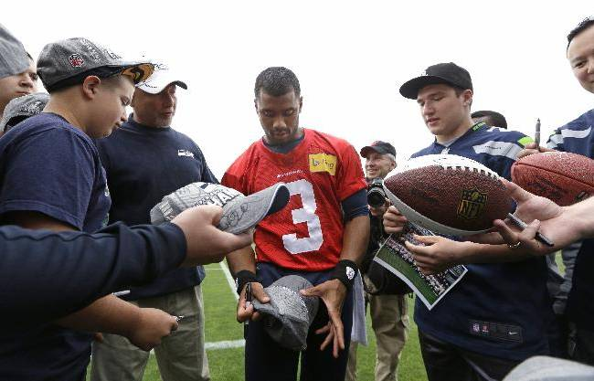 Seattle Seahawks quarterback Russell Wilson (3) signs autographs for members of the Darrington (Wash.) High School football team following a football minicamp practice Tuesday, June 17, 2014, in Renton, Wash