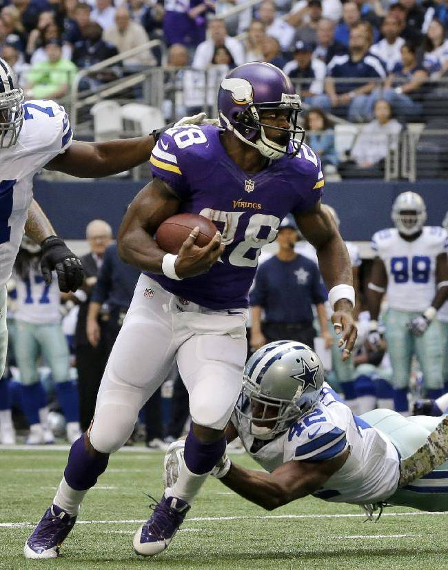 Minnesota Vikings running back Adrian Peterson (28) looks for running room under pressure from Dallas Cowboys' Everette Brown (71) and Barry Church (42) in the first half of an NFL football game, Sunday, Nov. 3, 2013, in Arlington, Texas