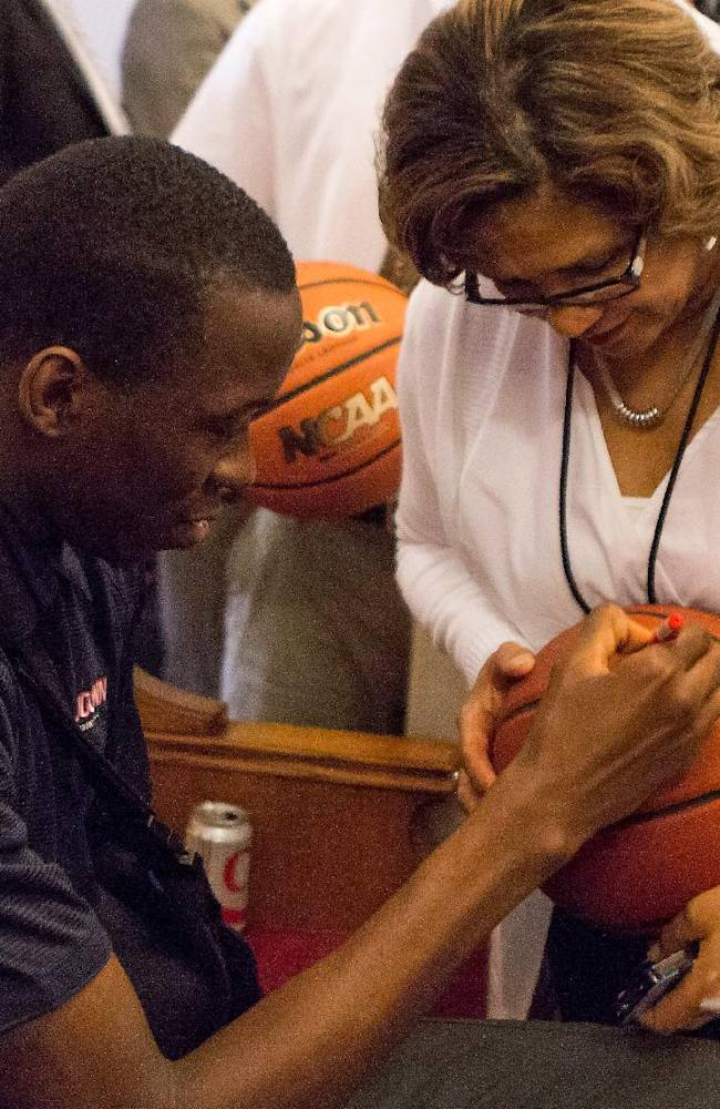 Connecticut's NCAA college basketball player Amida Brimah, left, signs an autograph for a fan during Husky Day at the Connecticut Capitol on Wednesday, April 30, 2014, in Hartford, Conn