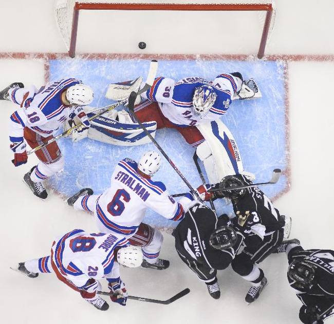 New York Rangers goalie Henrik Lundqvist, of Sweden, above, sits on the ice after the puck, shot by Los Angeles Kings right wing Justin Williams, below left, enters the goal during the first period in Game 5 of the NHL hockey Stanley Cup finals, Friday, June 13, 2014, in {city