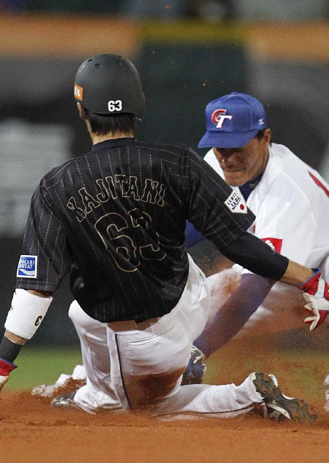 Japan's Takayuki Kajitani (63) is caught stealing at second by Taiwan's Kuo Ming-jen in the third inning of their exhibition baseball game at the Xinzhuang Baseball Stadium in New Taipei City, Taiwan, Friday, Nov. 8, 2013
