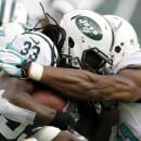New York Jets running back Chris Ivory, left, is wrapped up by Miami Dolphins defensive end Cameron Wake during the first half of an NFL football game on Sunday, Dec. 1, 2013, in East Rutherford, N.J The Associated Press