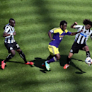 Newcastle United's captain Fabricio Coloccini, right, and 2Cheick Tiote, left, vies for the ball with Swansea City's Wilfred Bony, center, during their English Premier League soccer match at St James' Park, Newcastle, England, Saturday, April 19, 2014