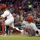 Cincinnati Reds' Joey Votto, right, scores on a triple by Jay Bruce as St. Louis Cardinals catcher Yadier Molina, left, waits for the throw during the first inning of a baseball game Tuesday, April 8, 2014, in St. Louis The Associated Press