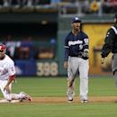 Milwaukee Brewers shortstop Jean Segura (9) argues a call with umpire Adrian Johnson, right, as Philadelphia Phillies' Ben Revere looks on from second base during the first inning of a baseball game on Wednesday, April 9, 2014, in Philadelphia The Associ