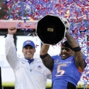 Boise State coach Chris Peterson, left, gestures as cornerback Jamar Taylor holds the championship trophy after the MAACO Bowl NCAA college football game against Washington, Saturday, Dec. 22, 2012, in Las Vegas. Boise State defeated Washington 28-26. (AP Photo/David Becker)