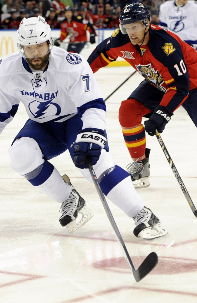 Tampa Bay Lightning defenseman Radko Gudas, left, of the Czech Republic, charges toward the puck in front of Florida Panthers right wing Joey Crabb during the first period of a preseason NHL hockey game Saturday, Sept. 21, 2013, in Tampa, Fla