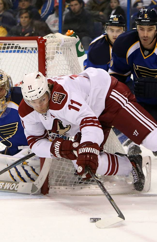Phoenix Coyotes center Martin Hanzal (11) tries to wrap around the net as he is defended by St. Louis Blues goaltender Jaroslav Halak, left, and defenseman Barret Jackman during the second period of an NHL hockey game Tuesday, Jan. 14, 2014, in St. Louis. The Blues won 2-1