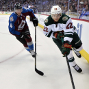 Minnesota Wild right wing Nino Niederreiter (22), from Switzerland, and Colorado Avalanche defenseman Tyson Barrie (4) chase the puck into the corner in the first period of Game 2 of an NHL hockey first-round playoff series on Saturday, April 19, 2014, in