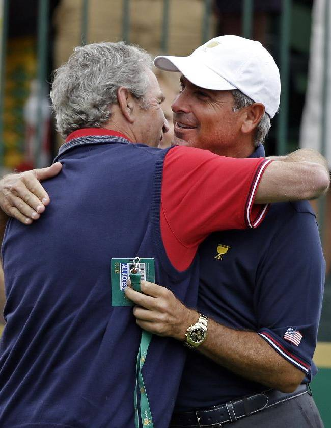 Former President George W. Bush, left, hugs United States captain Fred Couples before the four-ball matches against the International team at the Presidents Cup golf tournament at Muirfield Village Golf Club Thursday, Oct. 3, 2013, in Dublin, Ohio