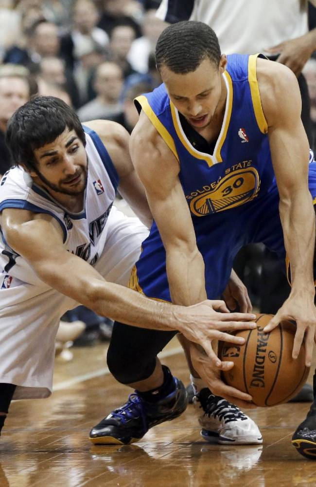 Minnesota Timberwolves' Ricky Rubio, left, of Spain, reaches for the ball against Golden State Warriors' Stephen Curry during the second half of an NBA basketball game Wednesday, Nov. 6, 2013, in Minneapolis. The Warriors won 106-93