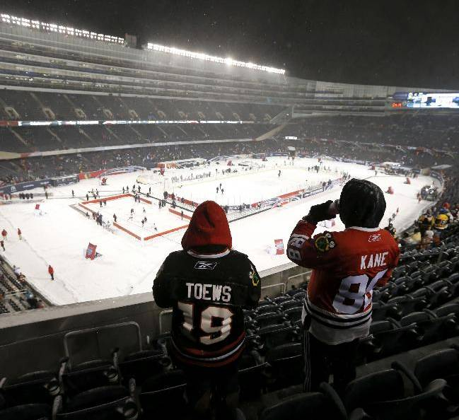 Two Chicago Blackhawks fans look out over the ice before an NHL Stadium Series hockey game between the Blackhawks and the Pittsburgh Penguins at Soldier Field on Saturday, March 1, 2014, in Chicago
