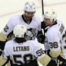 Pittsburgh Penguins' Jarome Iginla (12) celebrates a third period goal with teammates Kris Letang (58) and Jussi Jokinen (36) during NHL hockey playoff game action against the Ottawa Senators in Ottawa, Ontario, Wednesday, May 22, 2013. (AP Photo/The Canadian Press, Fred Chartrand)