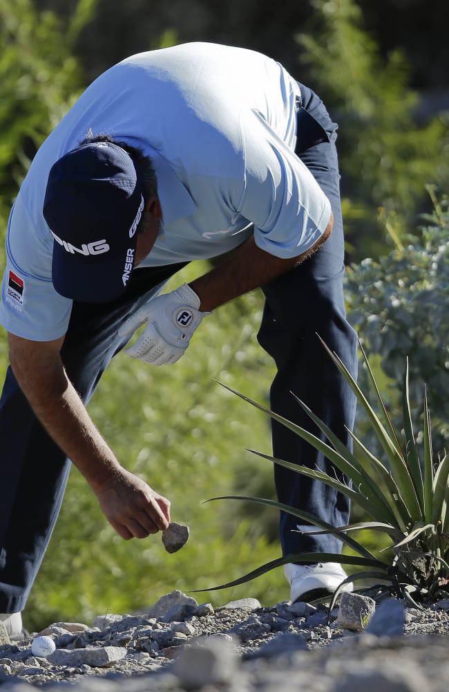 Angel Cabrera, of Argentina, picks away rocks from around his ball after hitting into the rocks near the 15th green in the first round of the Shriners Hospitals for Children Open golf tournament, Thursday, Oct. 17, 2013, in Las Vegas