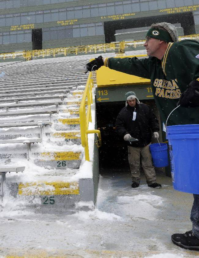 Michael Pauly, right, and Peter Harrsch put salt down at Lambeau Field before fans arrive for an NFL football game between the Green Bay Packers and the Pittsburgh Steelers Sunday, Dec. 22, 2013, in Green Bay, Wis