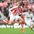 Swansea City's Tommy Carroll, right, and Stoke City's Peter Crouch battle for the ball during their English Premier League soccer match at the Britannia Stadium, Stoke, England, Sunday, Oct. 19, 2014