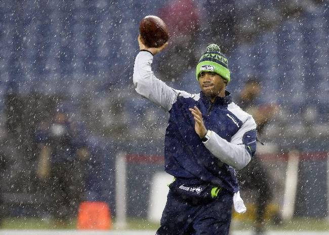 Seattle Seahawks quarterback Russell Wilson warms up in the rain before an NFC divisional playoff NFL football game against the New Orleans Saints in Seattle, Saturday, Jan. 11, 2014