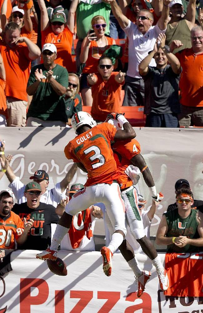 Miami's Stacey Coley (3) and Phillip Dorsett (4) celebrate after Dorsett scored during the first half of an NCAA college football game against Georgia Tech in Miami Gardens, Fla., Saturday, Oct. 5, 2013