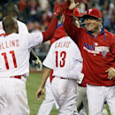 Philadelphia Phillies' Jimmy Rollins, left, gets a high-five from bench coach Larry Bowa, right, after hitting a solo home in the tenth inning to win a baseball game against the Miami Marlins, Saturday, April 12, 2014, in Philadelphia. The Phillies won 5