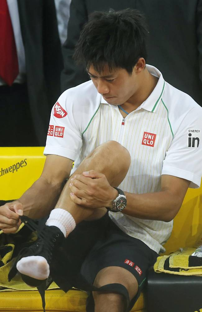 Kei Nishikori from Japan removes his ankle support as he retires from his Madrid Open tennis tournament final match against Rafael Nadal from Spain in Madrid, Spain, Sunday, May 11, 2014