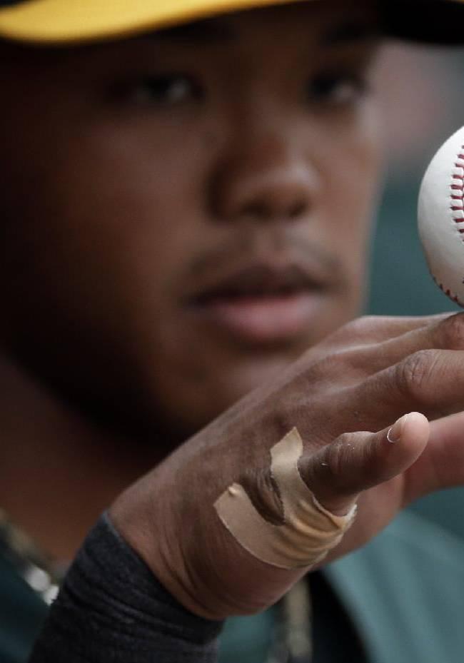 Oakland Athletics shortstop Addison Russell rolls a baseball on his hand in the dugout as the Athletics play the Arizona Diamondbacks in an exhibition spring training baseball game Thursday, March 6, 2014, in Scottsdale, Ariz