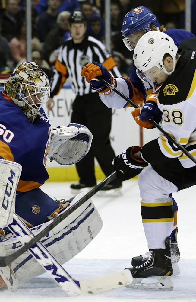 Boston Bruins' Jordan Caron, right, and New York Islanders' Calvin de Haan scuffle for the puck in front of goalie Kevin Poulin, left,  during the first period of the NHL hockey game, Monday, Jan. 27, 2014, in Uniondale, New York
