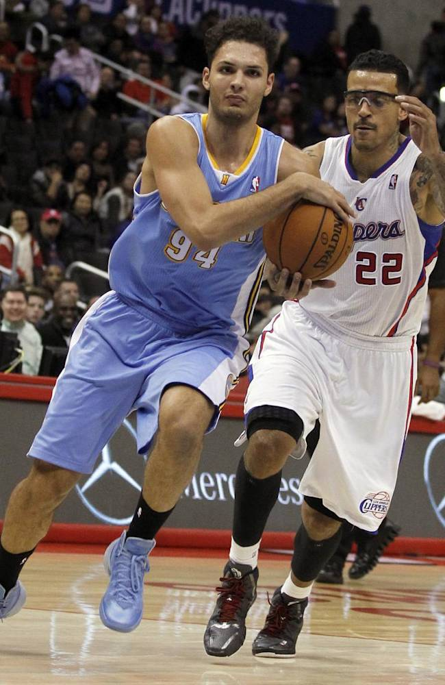 Denver Nuggets guard Evan Fournier (94), of France, drives to the basket with Los Angeles Clippers forward Matt Barnes (22) defending in the second half of an NBA basketball game in Los Angeles on Saturday, Dec. 21, 2013. Clippers won 112-91